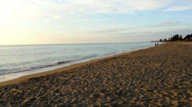 Couple walking in distance on empty beach — Stock Video