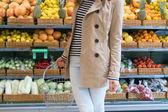 Flicka i snabbköpet väljer grönsaker och frukter — Stockfoto