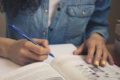Girl in a denim shirt reading a textbook and taking notes — Stock Photo