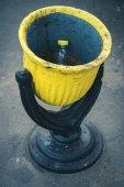 Black and yellow steel rubbish bin on the street — Stock Photo