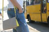 Young woman waiting for a bus at the bus stop close-up — Stock Photo