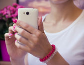 Modern white mobile phone with a camera in female hands with pur — Stock Photo