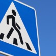 Road pedestrian crossing sign against the blue sky — Stock Photo #69795221
