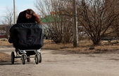 Young girl-mother walking with twins in a stroller — Stock Photo