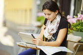 Young girl sitting in a cafe looking at tablet PC — ストック写真