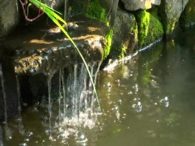 A small man-made waterfall in the stone pond city park — Stock Video