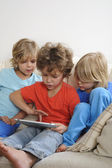 Three boys playing with a tablet — Stock Photo