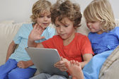 Three brothers with a tablet — Stock Photo