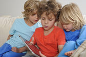 Watching older brother playing on a tablet — Stock Photo