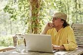 Pensive senior man with laptop — Stock Photo