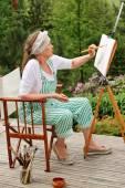 Senior woman painting outdoors — Stock Photo