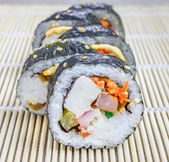 Kimbap on the bamboo mat closeup (Korean cuisine) — Stock Photo