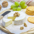 Soft brie cheese with sweet grapes, nuts and crackers — Stock Photo #71884495