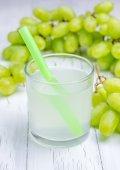 Bicchiere di succo di uva bianca e uva su fondo — Foto Stock