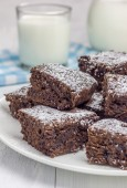 Sugar powdered homemade brownies with glass of milk — Stock Photo