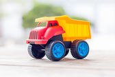 Plastic toy truck on a wooden background — Stock Photo