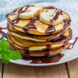 Stack of pancakes with banana and chocolate syrup — Stock Photo #74695069