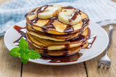Stack of pancakes with banana and chocolate syrup — Stock Photo