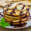 Stack of pancakes with banana and chocolate syrup, closeup — Stock Photo #75665771