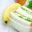 Lunch box with egg salad sandwiches, apple, banana and milk — Stock Photo #80554252