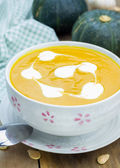 Pumpkin soup with sour cream on a wooden table — Stock Photo