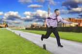 Running businessman in a hurry with modern city in background — Stock Photo