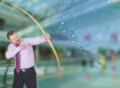 Businessman practicing archery with modern interior in background — Stock Photo