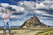 Man with guide book in a hand with Mont Saint-Michel, Lower Normandy, France in background — Stock Photo