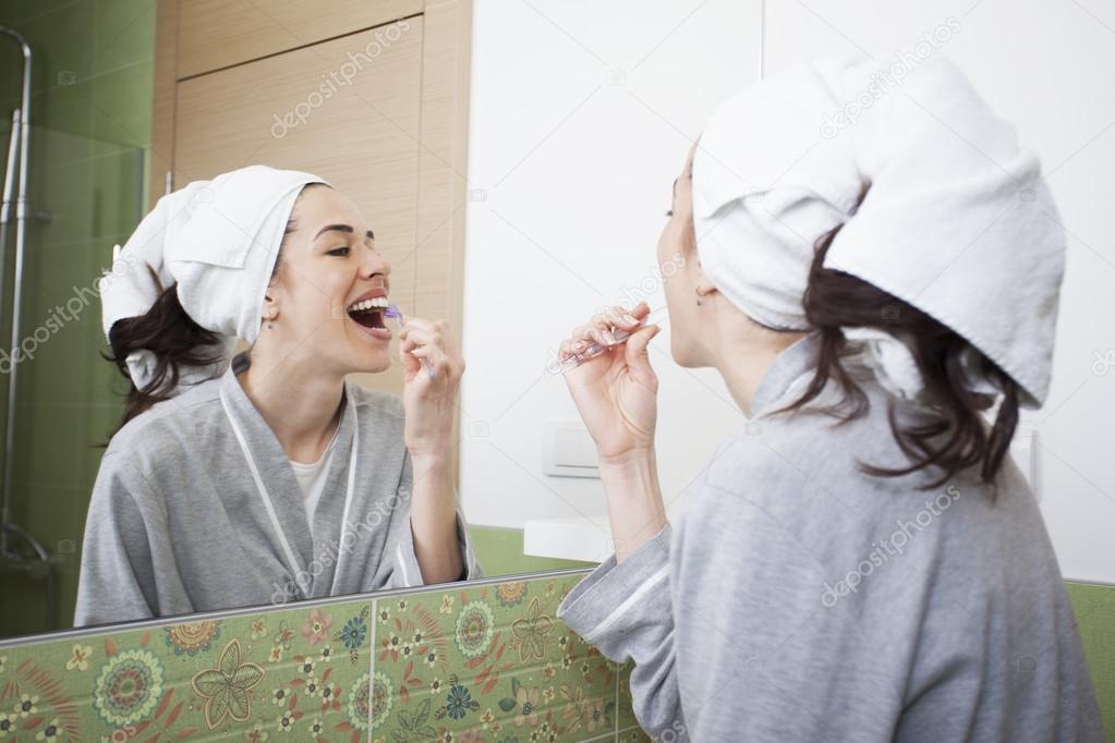 Jolie femme se brosser ses dents devant le miroir de salle for Derniere volonte devant le miroir