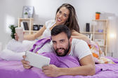 Happy young couple on bed sofa in ded room — Stock Photo