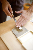 Wood carving on table with artist — Stock Photo