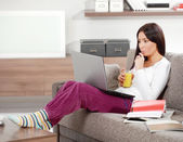 Brunette with lap top drinking juce — Stock Photo
