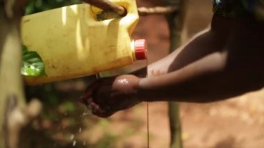 An African lady using a handwash station made from plastic containers — Stock Video