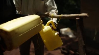 A man filling a water bottle to be used a handwash station in an African village — Stock Video