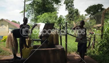 An African boy filling up yellow water containers at a well with his brothers and sisters — Stock Video
