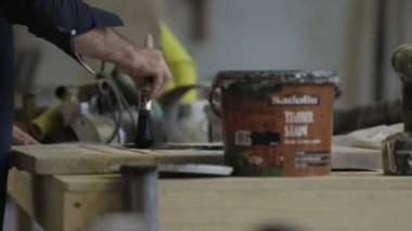 Man painting timber stain onto a piece of wood — Stockvideo