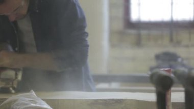 Man in workshop using a sander on  a piece of oak wood, Sheffield, England, October 2014 — Stock Video