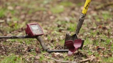 Metal detector and spade propped up in field ready for use — Stock Video