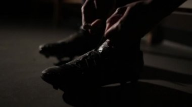 Footballer tying his laces getting ready for a match. Cinematic shot with lens flare — Stock Video