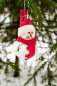 Toy snowman hanging on a snow-covered tree — Stockfoto