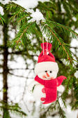 Toy snowman hanging on a snow-covered tree — Stock Photo