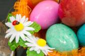 Colored eggs of stone in the basket — Photo