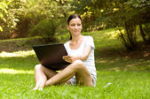 Woman working freelance.doing work in the park — Stock Photo