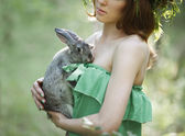 Beautiful model with a gray rabbit in her arms — Stock Photo