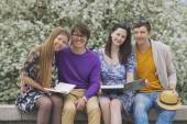 Four friends in the Park with books — Stock Photo