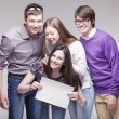 Group of young friends with advert board — Stock Photo #73159183