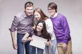 Group of young friends with advert board — Stock Photo