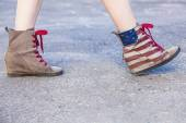 Female legs in sneakers with the design of the American flag on — Stock Photo