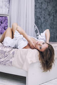 Female model beautiful sexy in white shirt on white bed in the m — Stock Photo