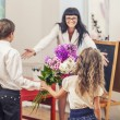 Boy and girl children give flowers as a school teacher in teache — Stock Photo #79231186